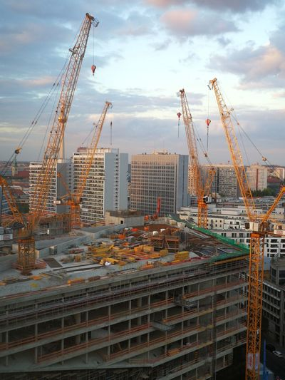 Cranes at construction site against buildings in city