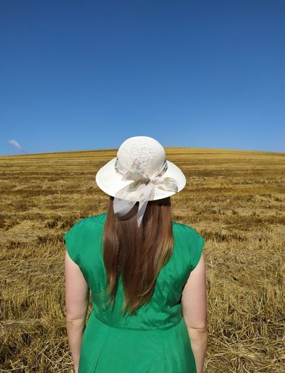 Rear view of woman wearing hat on field against clear sky