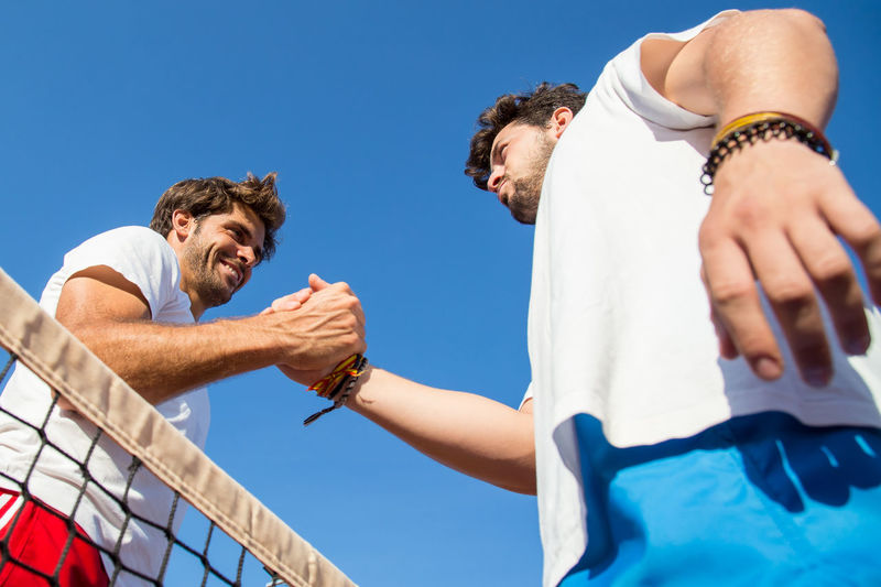 Low angle view of smiling tennis player holding hands at court
