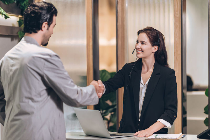 Receptionist welcome businessman at hotel front desk