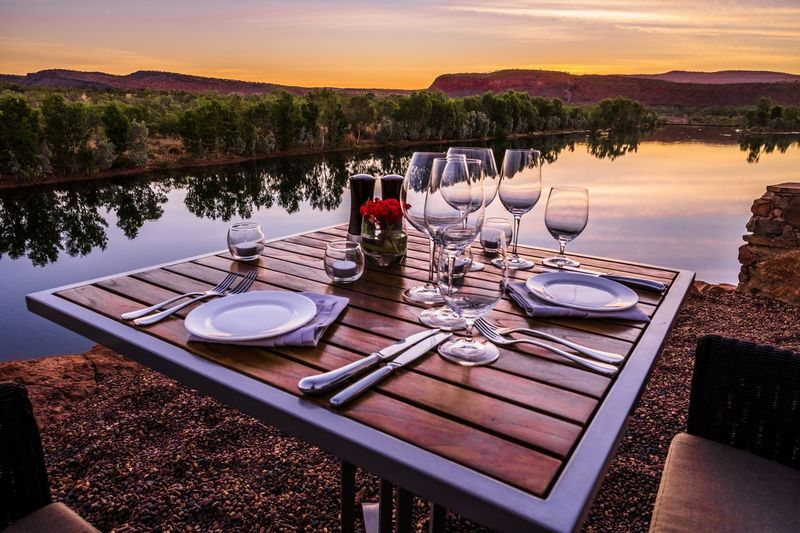 Chairs and table by lake against sky during sunset