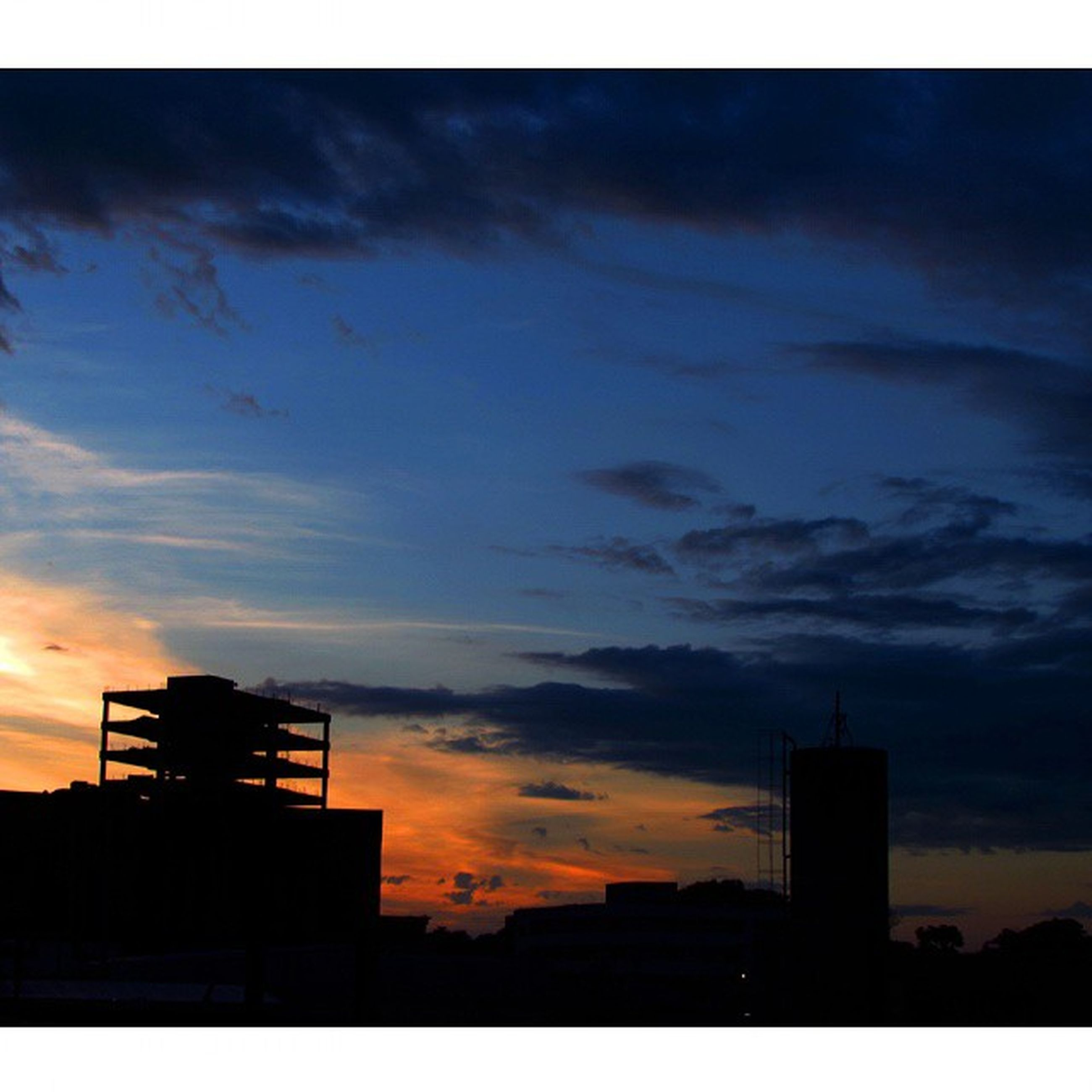 silhouette, building exterior, architecture, built structure, sunset, sky, low angle view, cloud - sky, cloud, city, building, cloudy, dusk, dramatic sky, outline, auto post production filter, orange color, transfer print, outdoors, residential structure