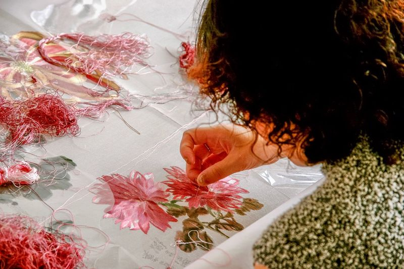 Chinese Silk Embroidery. Silk embroidery is a traditional Chinese art. Here a Chinese artist is preparing a colorful flower scene for display in a traditional rosewood frame. The completed art work is popular with locals & visitors who use them to decorate their homes & offices. The Traveler - 2018 EyeEm Awards Traditonal Chinese Arts & Crafts One Person Women Headshot Real People Portrait Adult Leisure Activity High Angle View Hair Red Lifestyles Plant Human Body Part Young Women Day Indoors