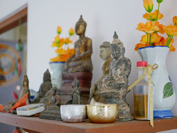 Selective focus of different sizes of Buddha images on a Buddha shelf ( Hing Phra ) at home in Thailand Religion Buddhism Buddha Statues Images Shelf Decorate Worship Sacred At Home Indoor Inside Displayed Belief Believe No People Flower Altar Beautiful Respected Sitting Dusty Grungy Symbol Symbolize