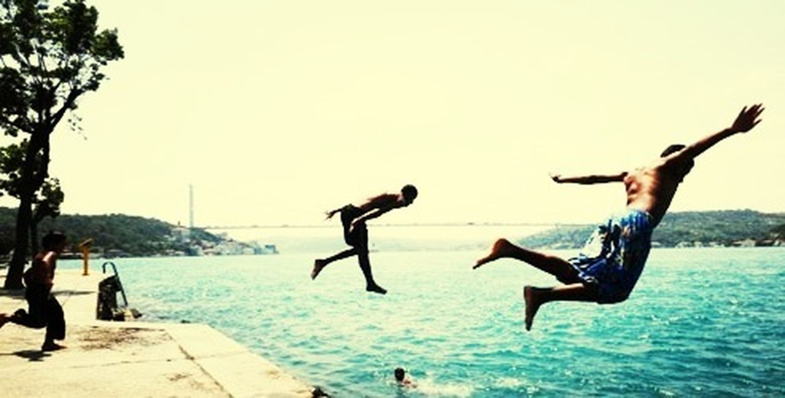 water, lifestyles, leisure activity, sea, enjoyment, mid-air, fun, clear sky, men, full length, jumping, flying, beach, vacations, motion, person, large group of people, carefree