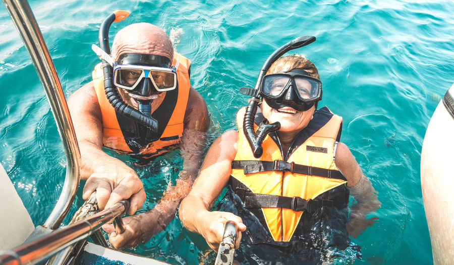 High angle portrait of couple snorkeling in sea