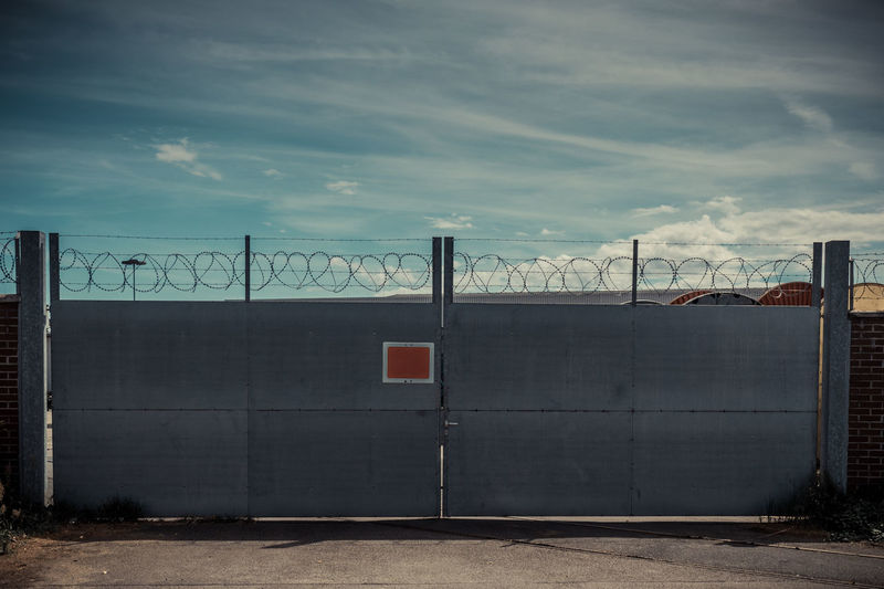 Barbed Wire Architecture Barbed Wire Built Structure Closed Closed Door Closed Gate Cloud Cloud - Sky Cloudy Day Gate No Entry No People No Trespassing Outdoors Protection Protective Safe Safe Place Security Security Gate Sky Stop