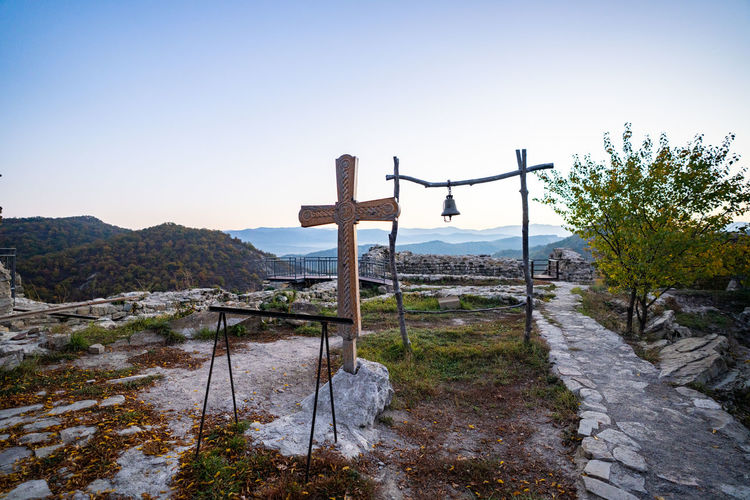 View of cross on landscape against sky