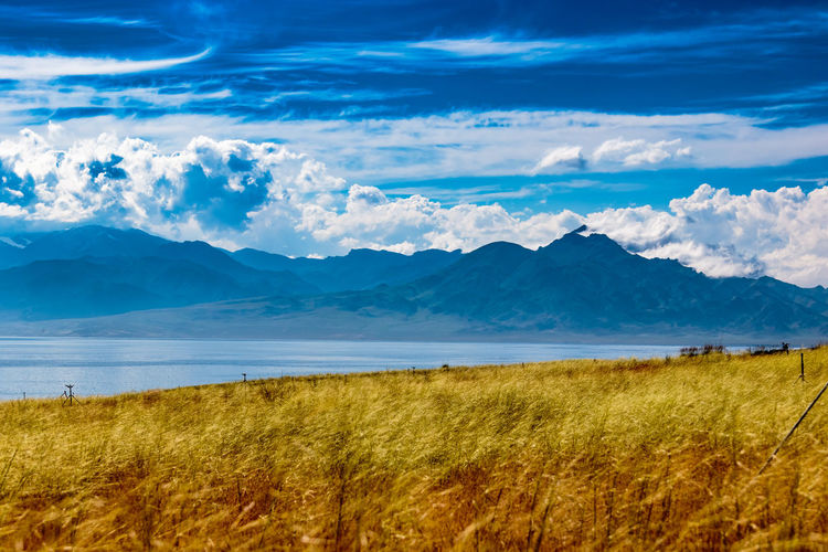 Beauty In Nature Blue Cloud Cloud - Sky Day Grass Grassy Growth Horizon Over Land Idyllic Landscape Mountain Mountain Range Nature No People Non-urban Scene Outdoors Plant Remote Rural Scene Scenics Sky Tranquil Scene Tranquility