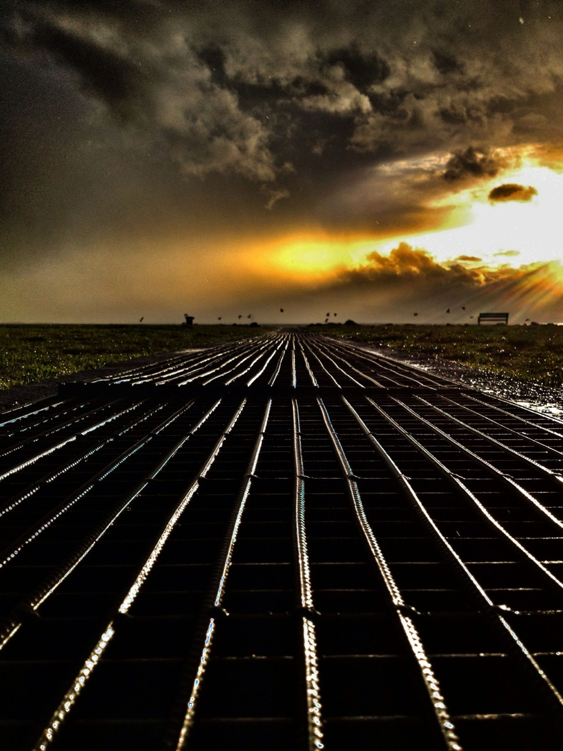 sunset, sky, cloud - sky, orange color, cloudy, dramatic sky, cloud, transportation, the way forward, diminishing perspective, weather, built structure, scenics, dusk, outdoors, beauty in nature, nature, no people, architecture, vanishing point