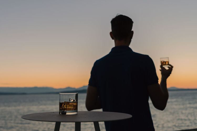 Rear View Of Man Holding Whiskey Glass By Sea During Sunset