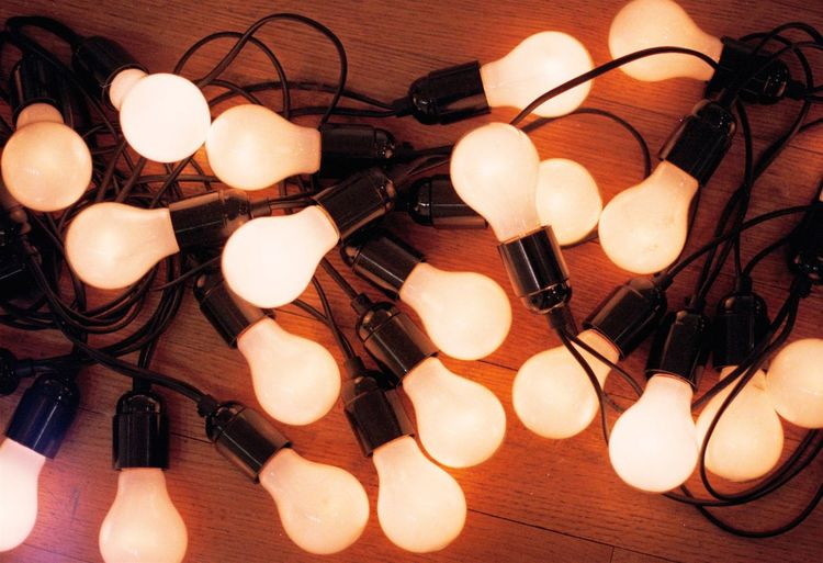 High angle view of illuminated light bulbs on wooden table
