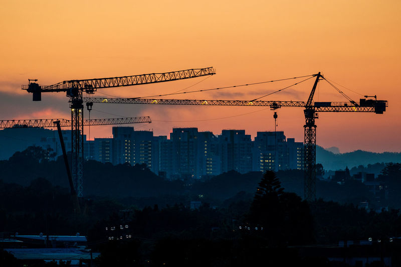 Cranes Against Buildings During Sunset