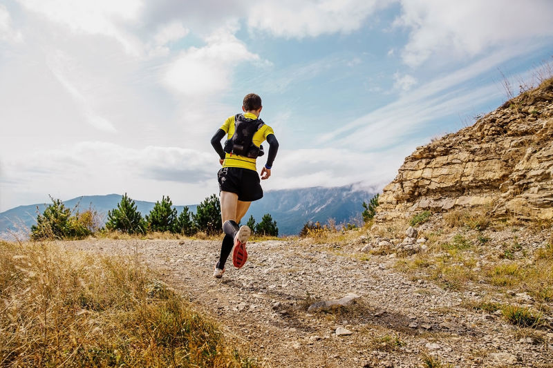 Rear view of man running mountain against sky