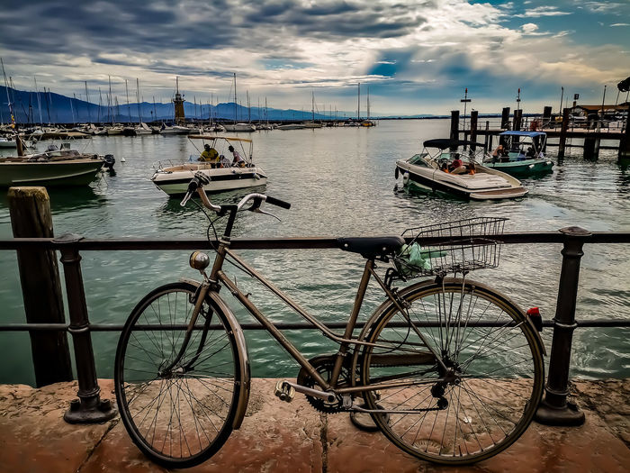 Bicycles on pier at harbor against sky