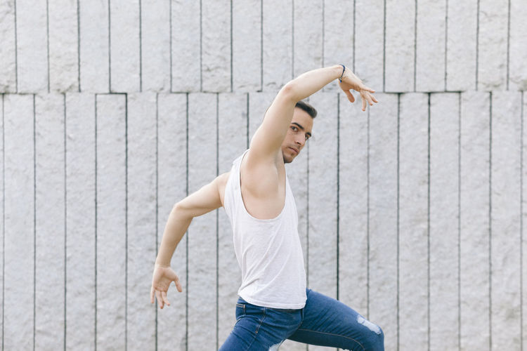 Portrait of young man with arms raised dancing by wall