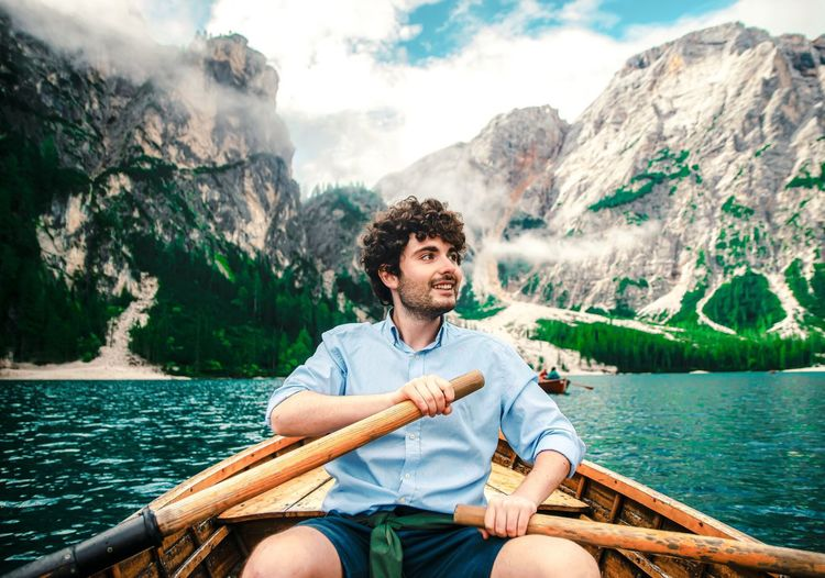 Young man sitting on boat against mountains
