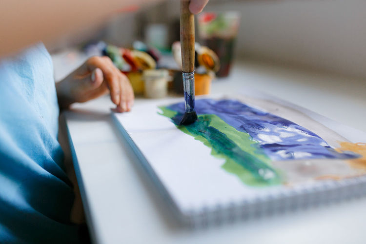 Midsection of boy painting at home