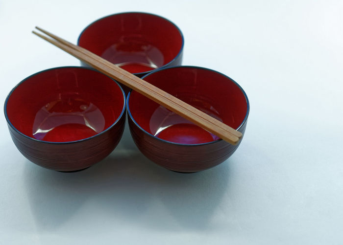 Three Japanese lacquer bowls and wooden chopsticks in front of a white background, isolated Isolated Japanese  Bowl Chopsticks Close-up Day Indoors  Lacquer No People Still Life Studio Shot Table White Background White Backround Wooden Food Stories