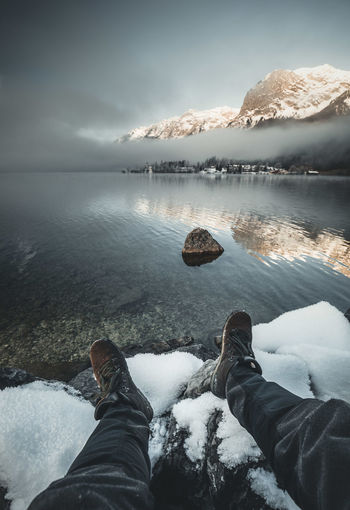 Low section of man sitting on snow by lake during winter