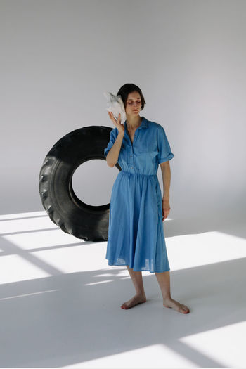 Indoors  Studio Shot Casual Clothing Women Clothing Fashion Young Adult Blue Young Women Beautiful Woman Hairstyle Dress Standing Full Length Front View One Person Holding Dress Tire Truck Tire Females Shell Sea Shells Girls Shadow Light And Shadow White Background Wheel barefoot Lifestyles Fashion Woman Girl Eyes Closed  Listening Calm Tranquility Tranquil