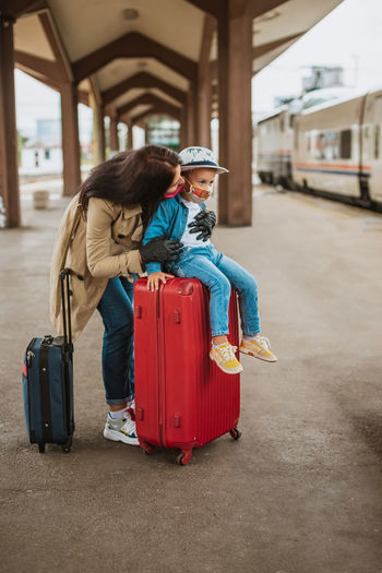 Full length of mother with son wearing mask standing on railroad station platform