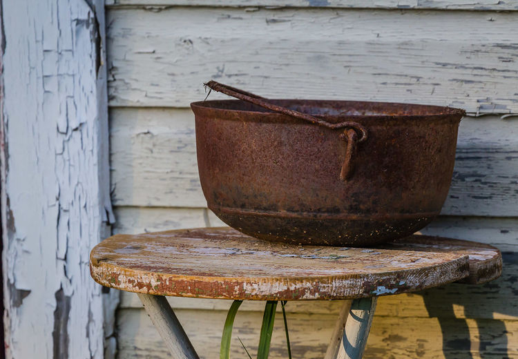 Close-Up Of Rusty Metallic Bowl On Table Against Wall