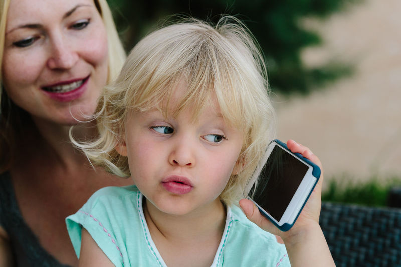 Close-Up Of Cute Girl Holding Mobile Phone At Home