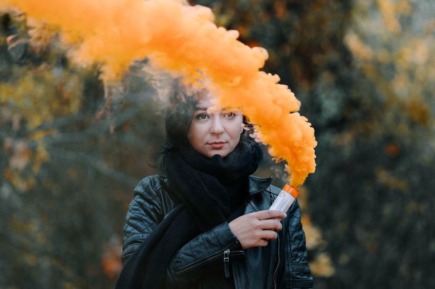 Autumn Orange Color Orange Women Smoke Smoke - Physical Structure Smoke Bomb Smokebomb One Person One Woman Only Young Women Warm Clothing Portrait Winter Cold Temperature Looking At Camera Talcum Powder Multi Colored Front View Firework - Man Made Object Entertainment Smoke Stack Autumn Mood