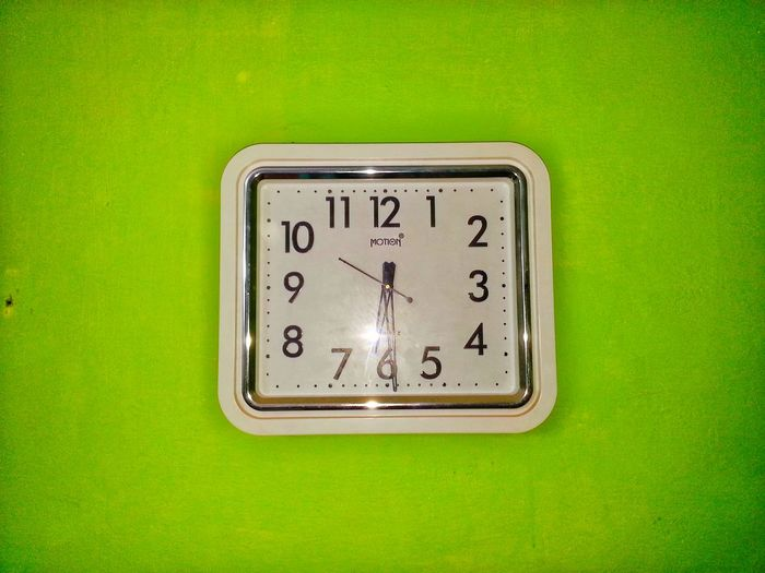 Close-up of clock in a green background showing time 6.30 .
