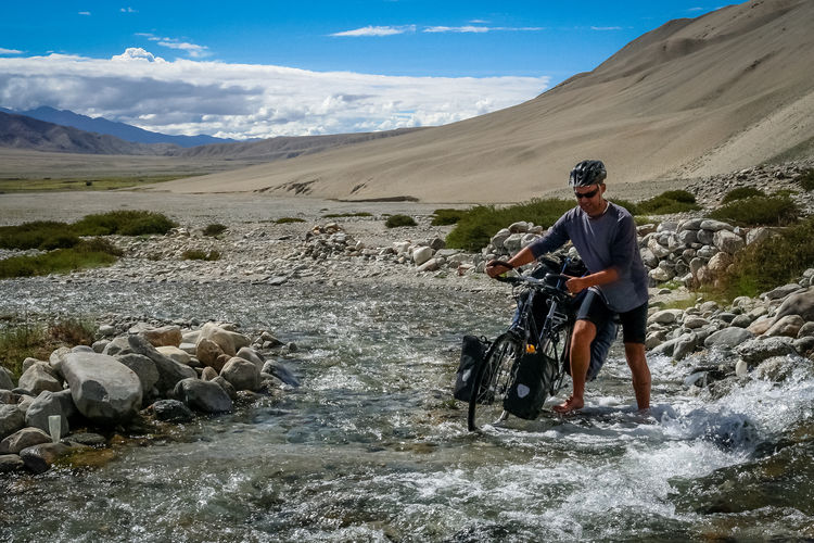 Man with bicycle crossing river against mountains