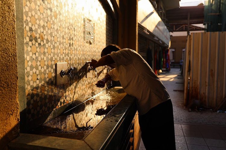 Man drinking water at fountain