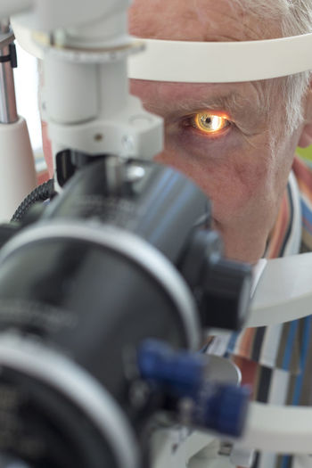 Close-up of man looking through optometrist phoropter