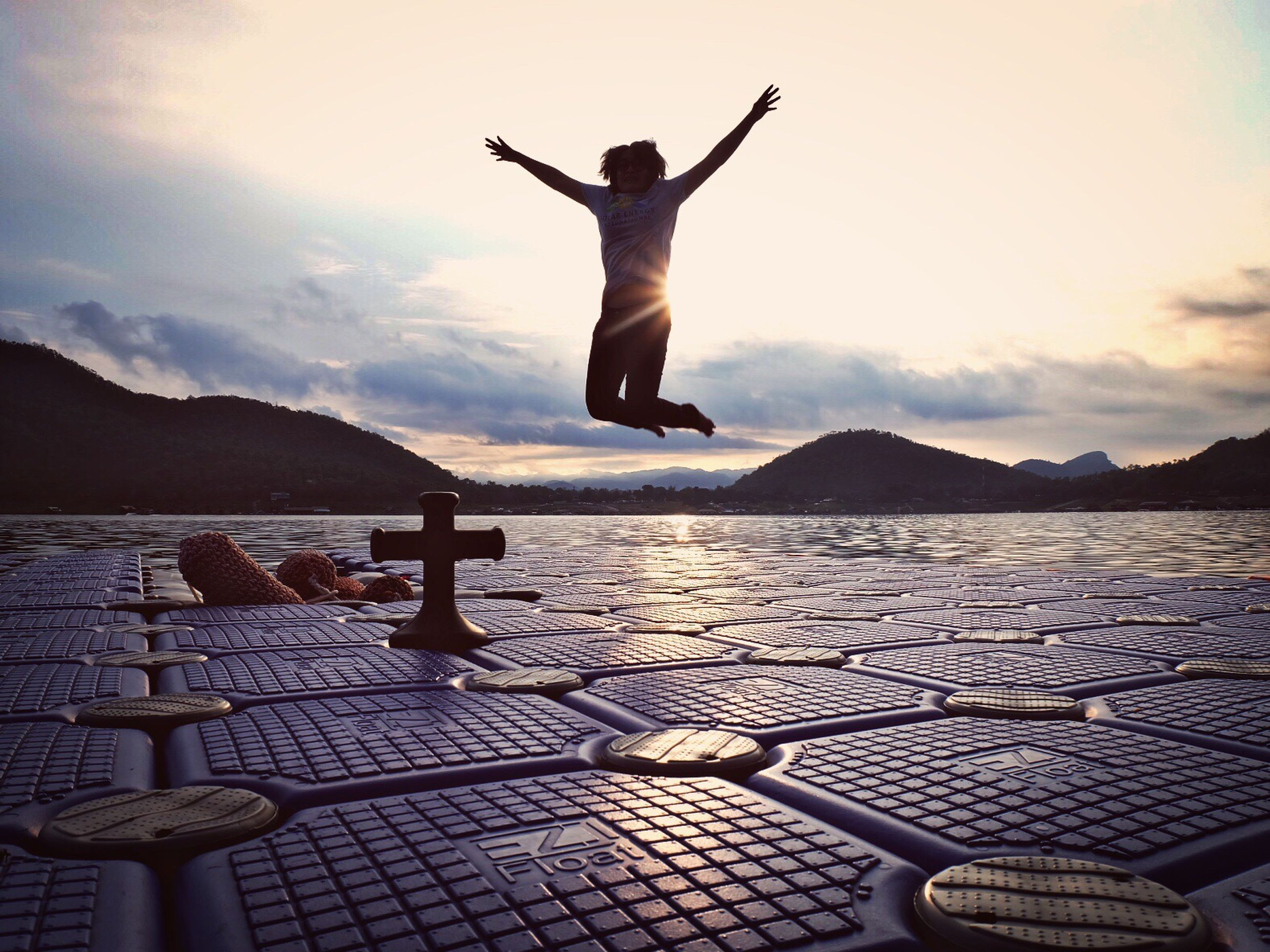 full length, lifestyles, jumping, mid-air, leisure activity, arms outstretched, sky, arms raised, enjoyment, freedom, balance, fun, cloud - sky, casual clothing, vacations, cloud, mountain, skill, outdoors, day, nature, tranquil scene