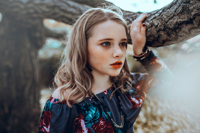 Blond Hair Contemplation Day Focus On Foreground Hair Hairstyle Headshot Leisure Activity Long Hair Looking At Camera Nature One Person Outdoors Portrait Tree Tree Trunk Trunk Women Young Adult