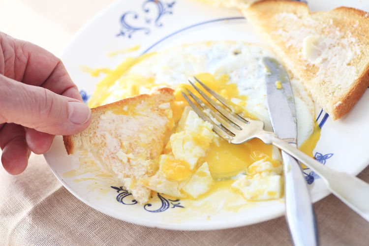Man eats runny eggs and toast pov American Breakfast Breakfast Buttered Toast Close-up Day Diner Fabric Fingers Food Fork Freshness Fried Eggs Healthy Eating Human Hand Meal Morning Napkin Natural Light One Person Plate Point Of View Ready-to-eat Runny Eggs Silverware  Yellow