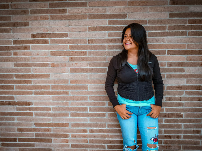 beautiful EyeEm Selects City Young Women Portrait Smiling Standing Beautiful Woman Cheerful Wireless Technology Youth Culture Beauty Denim Jacket Brick Brick Wall Looking Around Casual