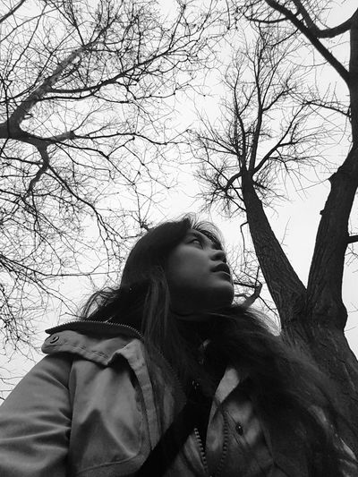 Low Angle View Of Woman Wearing Warm Clothing While Standing Against Trees