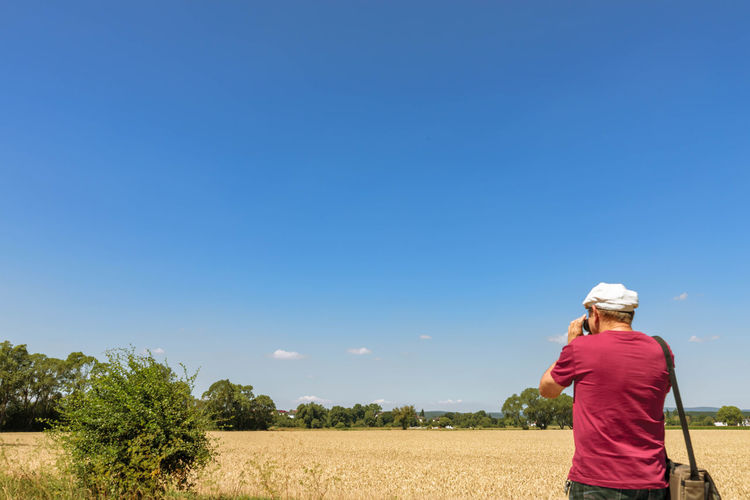 rear view of man on field against sky Beauty In Nature Blue Casual Clothing Copy Space Day Feld Field Hat Juli Land Leisure Activity Lifestyles Nature One Person Outdoors Plant Real People Rear View Scenics - Nature Sky Solitärbäume Sunlight Three Quarter Length