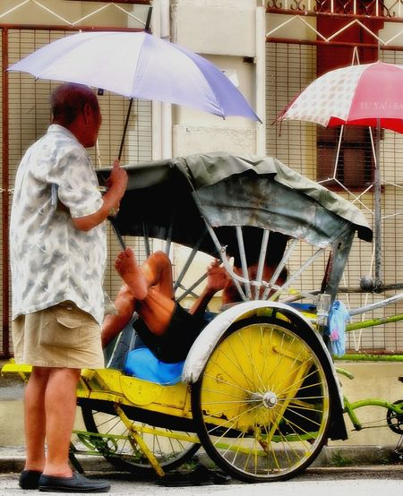 Man holding umbrella on wet street