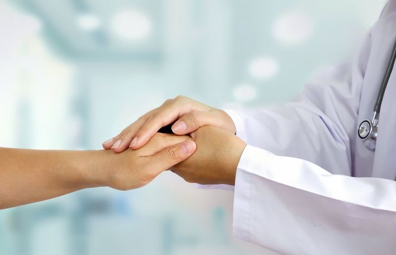 Midsection of doctor and patient holding hands
