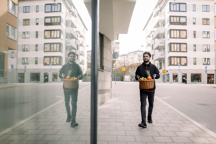Full length portrait of man standing on street in city