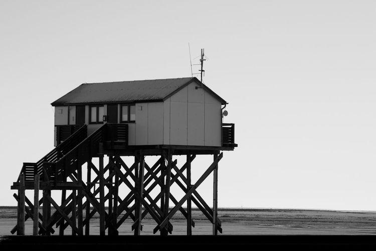 Hut on beach by sea against clear sky
