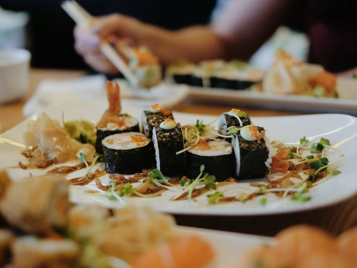 Cropped hand having sushi at table