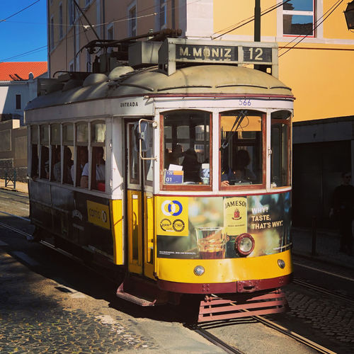 Tram in Lisbon, Portugal Lisbon Portugal Tram Building Exterior Architecture Public Transportation City Mode Of Transportation Transportation Cable Car Track Railroad Track Built Structure Rail Transportation Sunlight Day Street Land Vehicle Yellow Nature Outdoors Window Text Incidental People