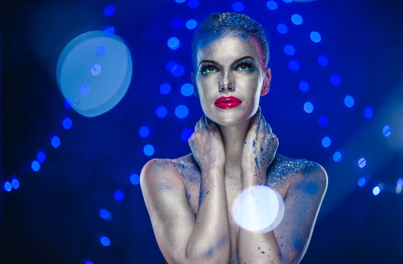 Naked Woman With Glitter Against Blue Background