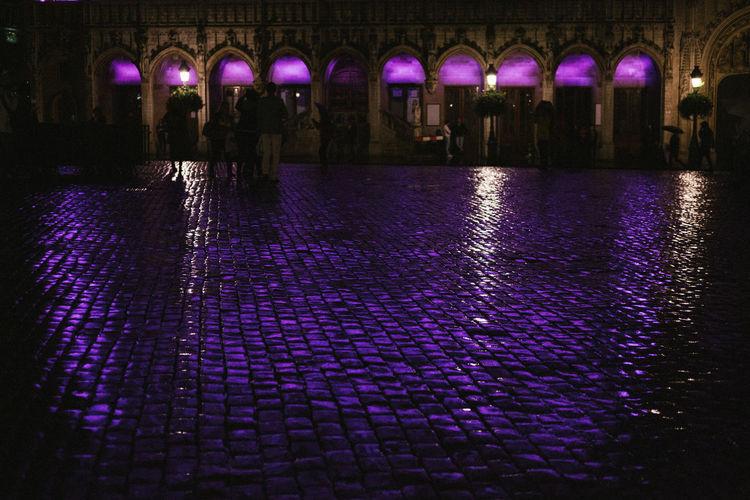 Illuminated lights on wet street at night