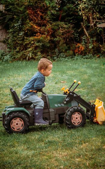 Boy with toy car on field
