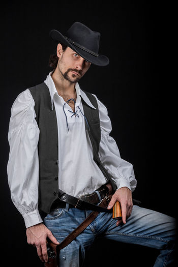 Handsome young man. This is an American cowboy. A vow to a white shirt, brown waistcoat and blue jeans. Black shoes on the feet. Carries a shtyapa, on a belt two pistols. The hair is of medium length; on the face is a beard and mustache. Authentic photo. Culture of America. Cowboy Wild West America American Gun National Authentic Moments Lifestyles Lifestyle One Person Candid Authentic Hat Clothing Three Quarter Length Front View Young Men Men Young Adult Black Background Looking Males  Casual Clothing Beard Mid Adult