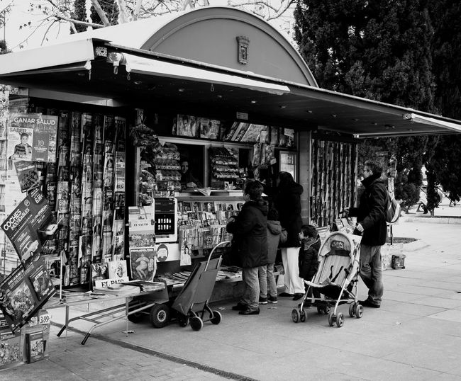 Newsstand in Madrid Streetphoto_bw Street Photography Streetphotography Newsstand Black And White Bnw Kiosco  Leisure Activity Lifestyles Real People Day Outdoors Standing Building Exterior Large Group Of People People City